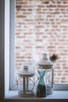 Tiro vertical seletivo closeup de lâmpadas de lanterna de vidro grande e médio em um peitoril da janela