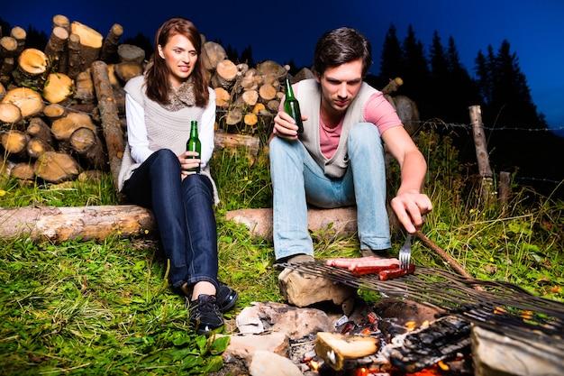 Tirol - jovem casal sentado no prado alpino de uma montanha na fogueira nos alpes da baviera, apreciando o romântico pôr do sol noturno do panorama em momentos de lazer ou férias