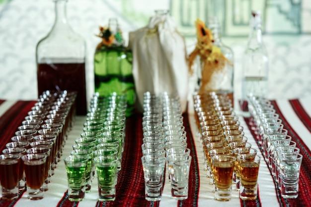 Tiros com diferentes bebidas coloridas estão na mesa bordada