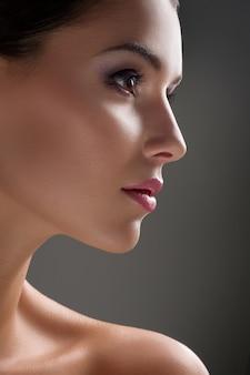 Tiros de beleza de estúdio de uma jovem mulher com uma pele impecável