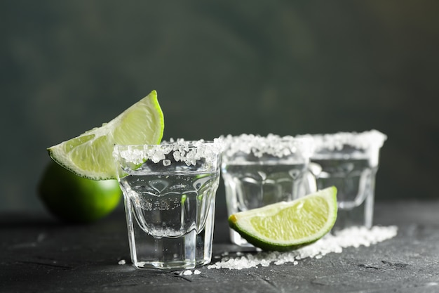 Tiros de tequila com fatias de sal e limão no preto