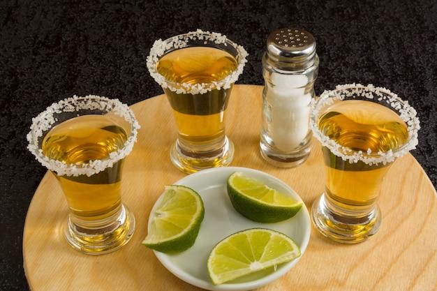 Tiros de tequila ouro na placa de madeira redonda