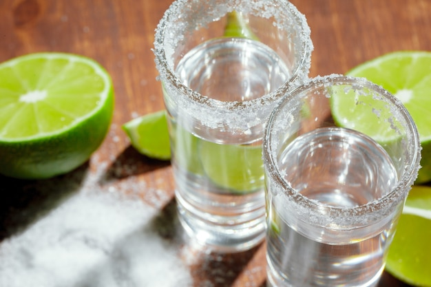 Tiros de tequila prata com fatias de limão e sal na placa de madeira