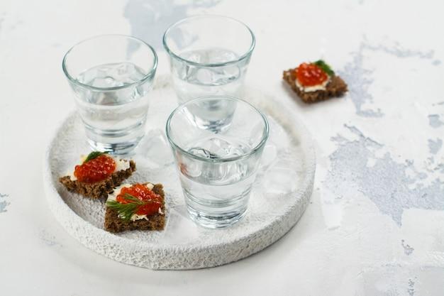 Tiros de vodka e sanduíche de caviar vermelho