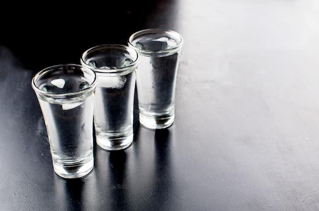 Tiros de vodka na mesa preta