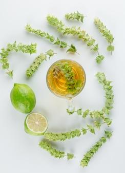 Tisana com folhas, limão em um copo de vidro em branco, vista superior.