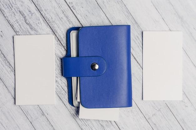 Titular de cartão de visita azul com papel timbrado em uma vista superior da parede de madeira.