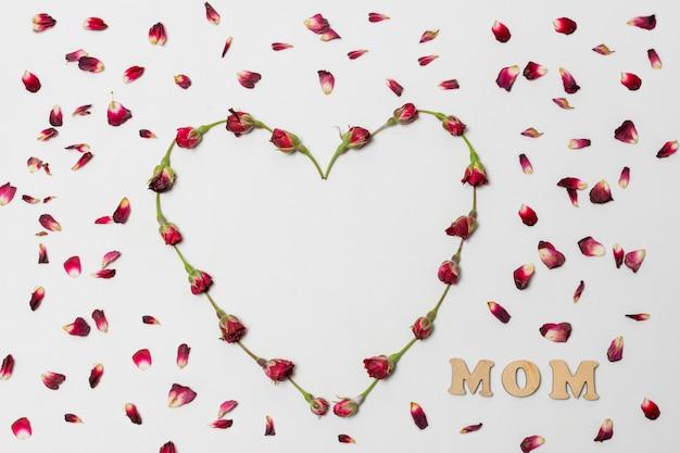 Título da mãe entre o coração decorativo vermelho das flores entre as pétalas