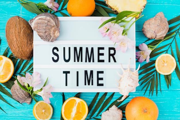 Título de horário de verão na mesa entre folhas de plantas perto de frutas com flores