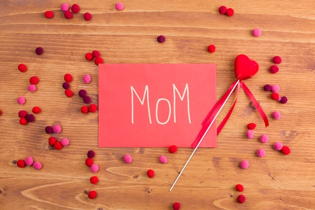 Título de mãe em papel rosa perto de coração decorativo