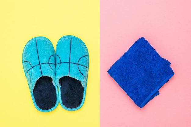 Toalha azul escura e chinelos azuis na superfície rosa e amarela. conjunto de acessórios de manhã.