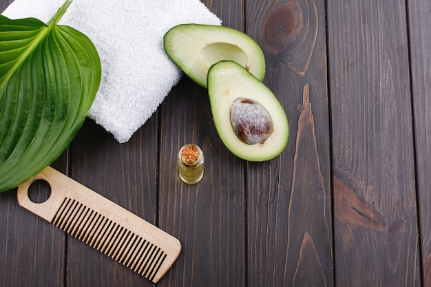 Toalha branca, abacate, garrafa de vidro pequena e pente de madeira para cabelo deitar em uma mesa de madeira
