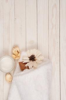 Toalha branca cosméticos acessórios de banheiro cenário de espaço de madeira.