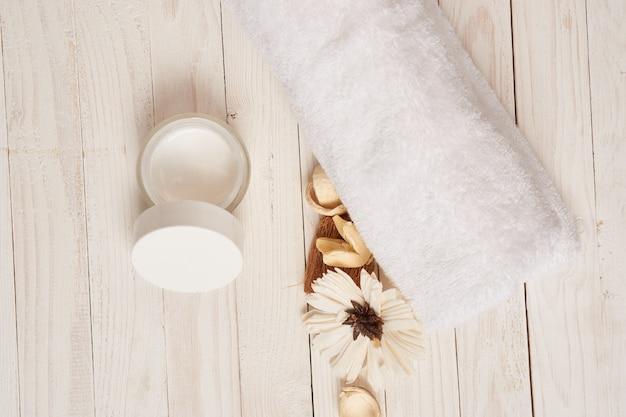 Toalha branca cosméticos acessórios de banheiro cenário de fundo de madeira.