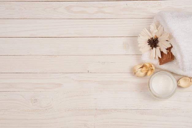 Toalha branca cosméticos acessórios de banho cenário de madeira. foto de alta qualidade