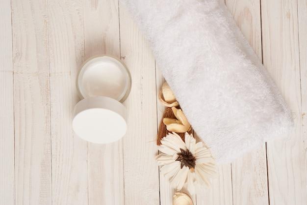 Toalha branca cosméticos acessórios de banho cenário de madeira.