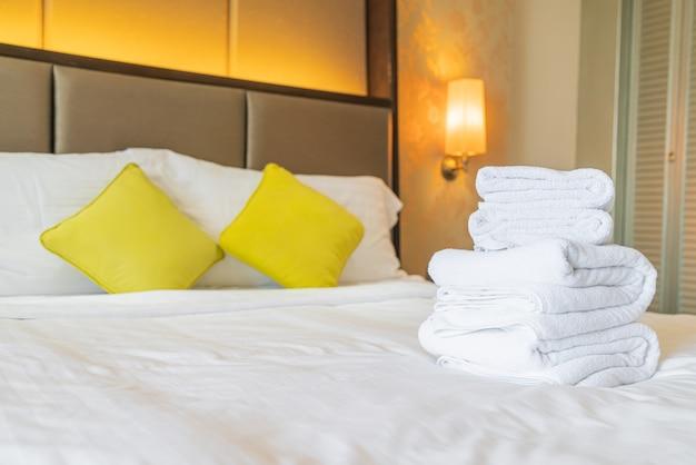 Toalha branca dobrada na cama em hotel resort