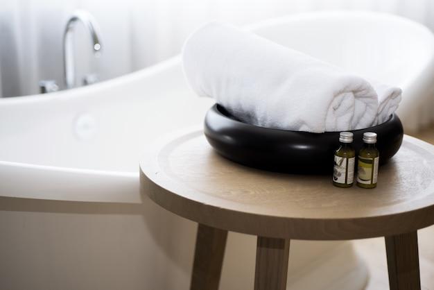 Toalha branca e óleo de banho de massagem na mesa na casa de banho