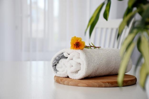 Toalha branca fresca enrolada na placa de madeira, flor de laranjeira e janela de tule no fundo. copie o espaço.