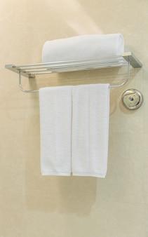 Toalha branca limpa em um cabide preparado no banheiro.