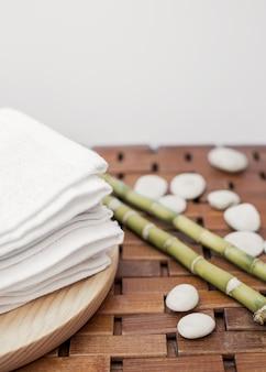 Toalha branca; planta de bambu e seixos na superfície de madeira