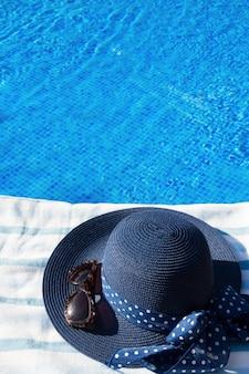 Toalha, chapéu de verão e óculos de sol perto da piscina