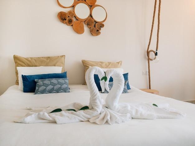 Toalha cisnes brancos em forma de coração na cama do hotel