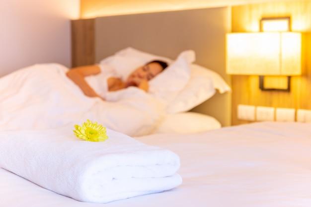 Toalha com flor na cama no quarto de hotel com mulher dormindo