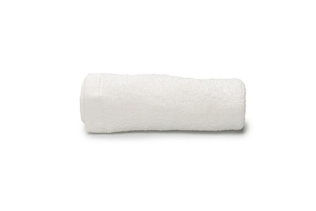 Toalha de algodão fofo branco isolada em um fundo branco. spa e resort.