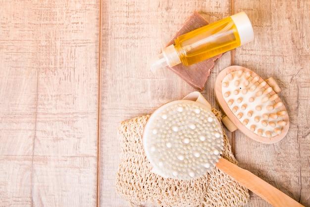 Toalha de banho de malha, sabonete de cacau caseiro, massageador de madeira e óleo corporal e escova para massagem anticelulite seca em uma mesa de madeira