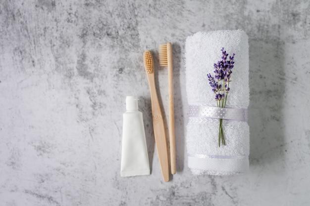 Toalha de banho torcida com escovas de dentes de bambu e creme dental em cinza claro. conceito de spa.