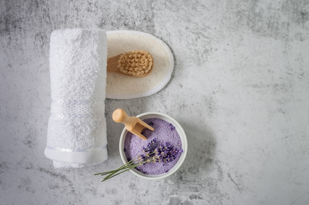Toalha de banho torcida com sal de banho e pincel sobre cinza claro.