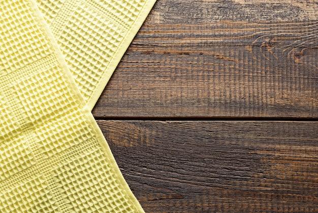 Toalha de cozinha amarela em fundo de madeira marrom com espaço de cópia