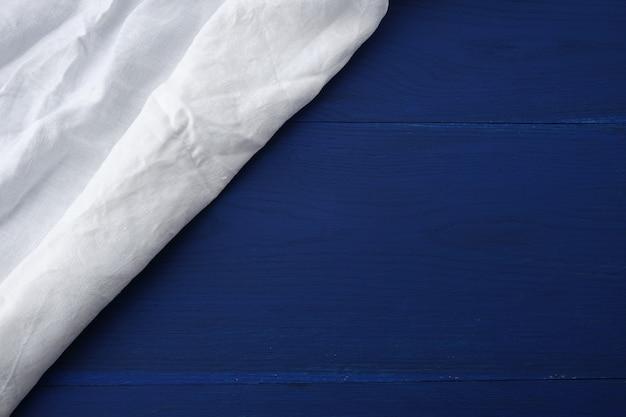 Toalha de cozinha branca têxtil dobrada sobre uma mesa de madeira azul de fundo de placas