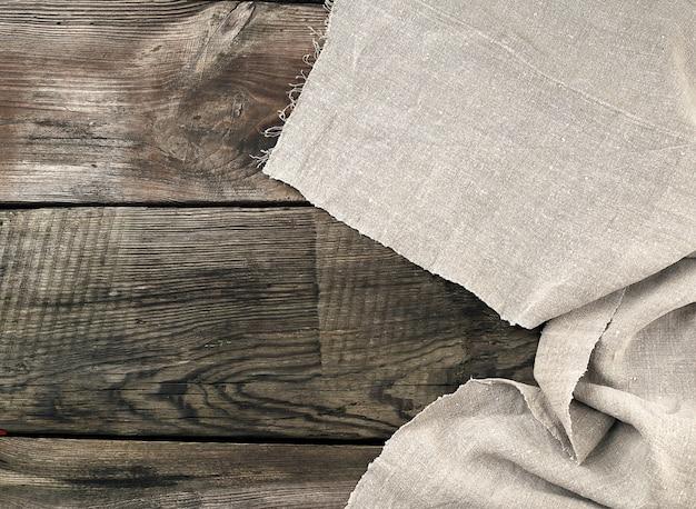 Toalha de cozinha cinza têxtil dobrada sobre uma mesa de madeira cinza de tábuas velhas