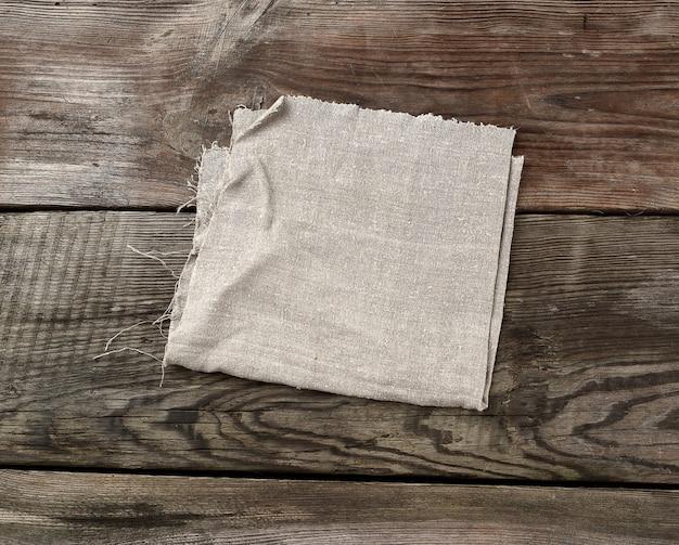 Toalha de cozinha cinza têxtil dobrada sobre uma mesa de madeira cinza