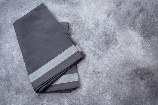 Toalha de cozinha cinzenta no fundo de pedra cinzento da tabela.