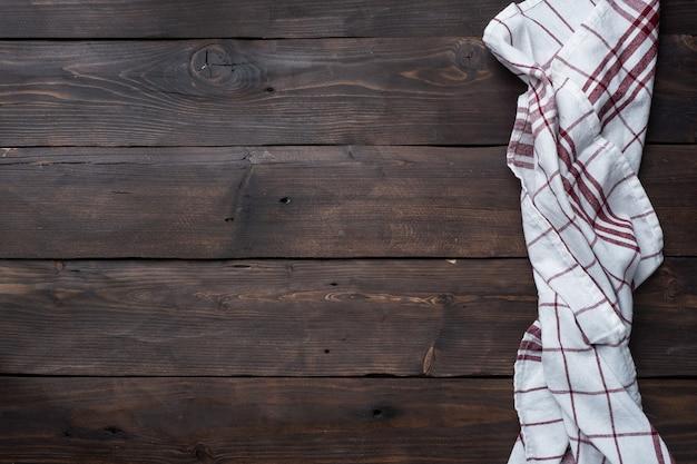 Toalha de cozinha de guardanapo têxtil. fundo de mesa rústica de madeira. copie o espaço.