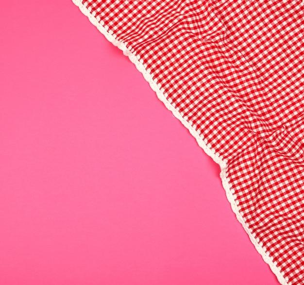 Toalha de cozinha quadriculada vermelha branca sobre um fundo rosa