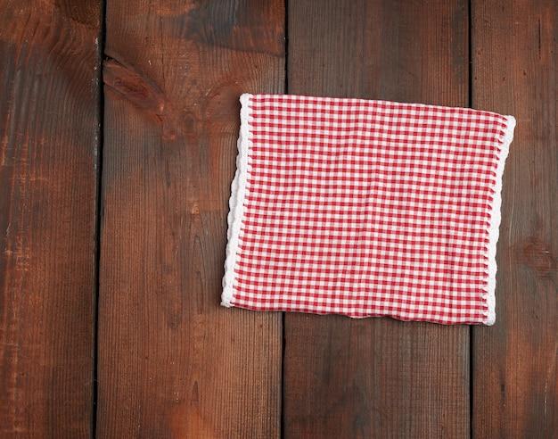 Toalha de cozinha quadriculada vermelha branca sobre uma superfície de madeira marrom