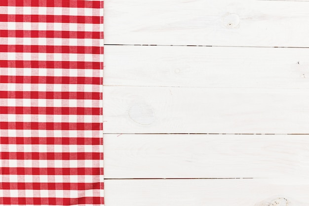 Toalha de cozinha quadriculada vermelha na mesa de madeira branca