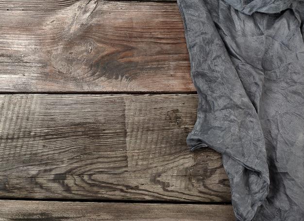 Toalha de cozinha têxtil preto sobre um fundo de madeira de tábuas cinzas velhas