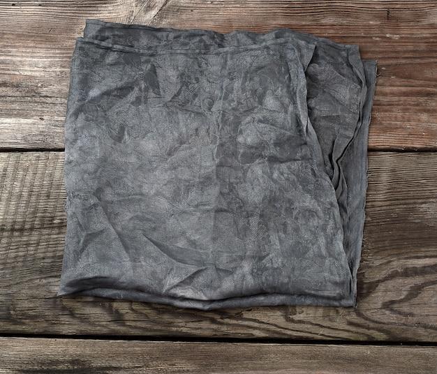 Toalha de cozinha têxtil preto sobre uma superfície de madeira