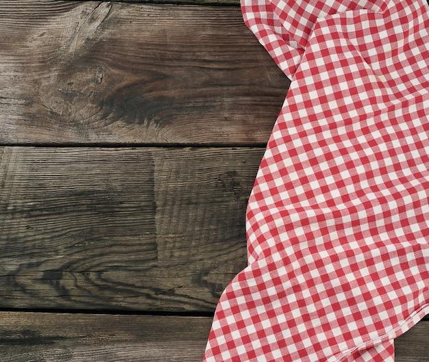Toalha de cozinha têxtil vermelho e branco em uma superfície de madeira