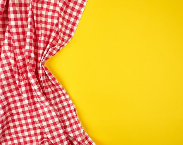 Toalha de cozinha xadrez vermelha branca sobre um fundo amarelo