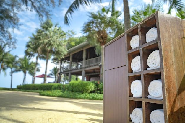 Toalha de enrolar na caixa quadrada de madeira no jardim privado da praia do hotel, preparada para uso do viajante.