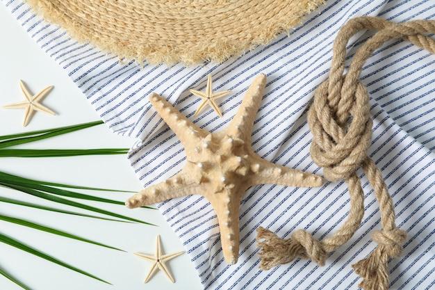 Toalha de mesa, chapéu de palha, estrelas do mar, corda do mar e folhas de palmeira na superfície branca, vista superior e closeup. férias de verão