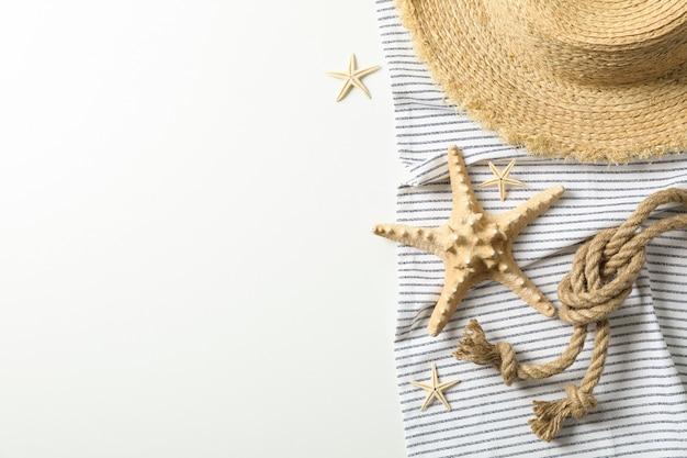 Toalha de mesa com chapéu de palha, estrelas do mar e corda do mar sobre fundo branco, espaço para texto e vista superior. férias de verão