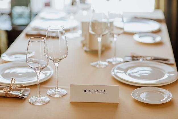 Toalha de mesa de almoço com pratos brancos, copos e placa de nome recebida em restaurante. o foco está na placa de identificação.