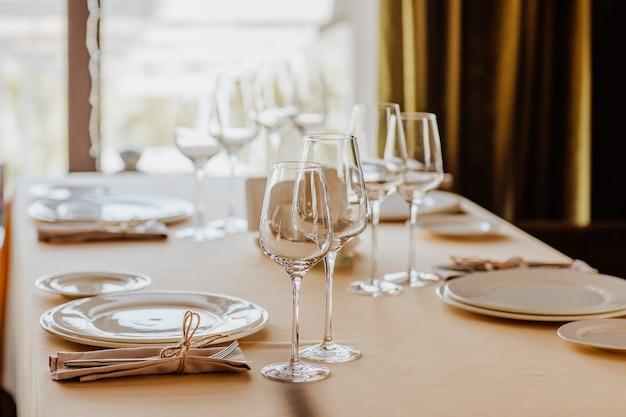 Toalha de mesa de almoço com pratos brancos, copos e placa de nome recebida em restaurante.